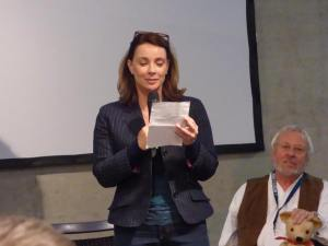 Nicola Bryant (with Terry Molloy in background) talking at a panel. (Photo by Pascal Salzmann)